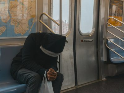 man with head down sitting on a train
