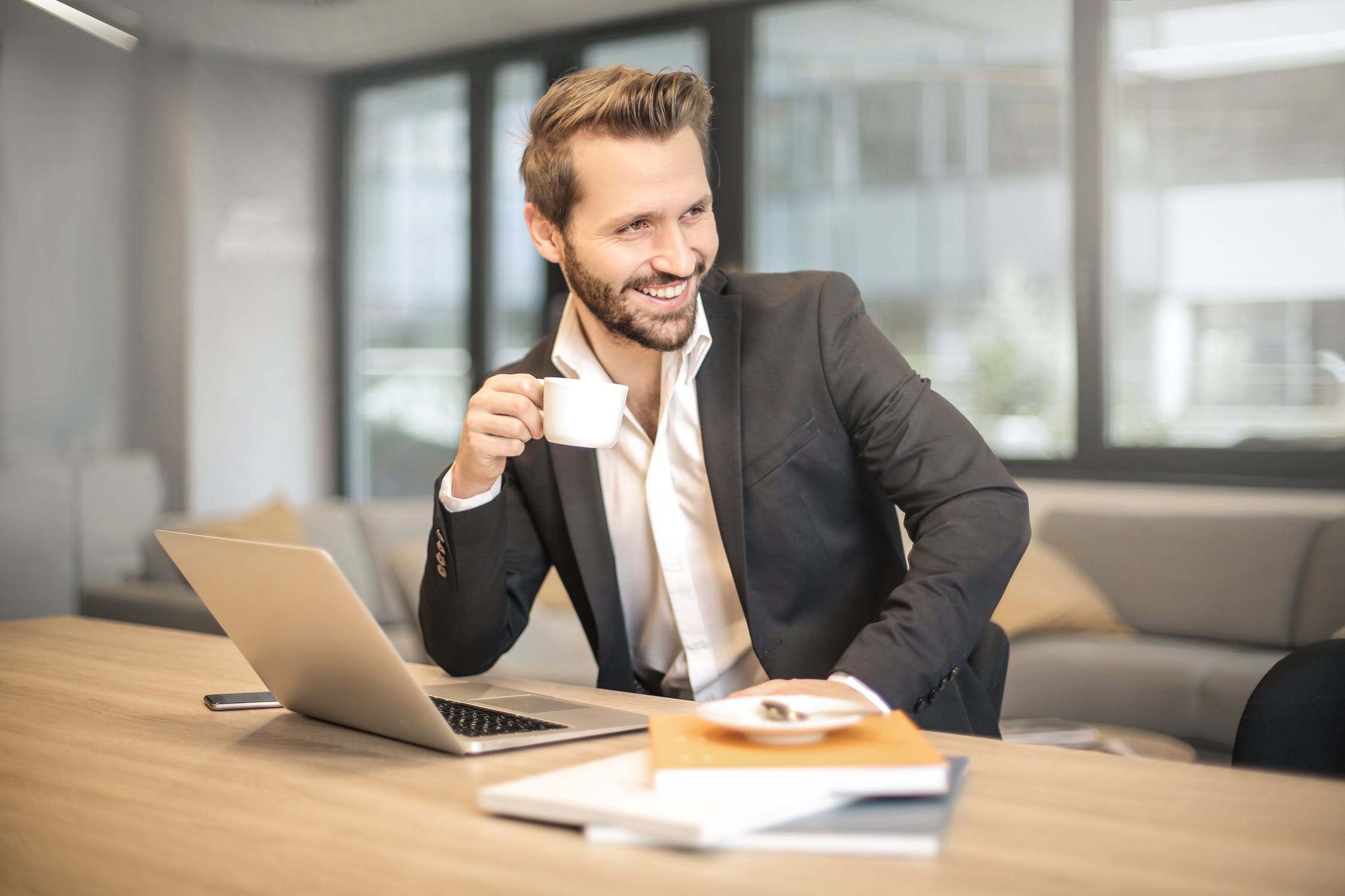man in suit with coffee at desk