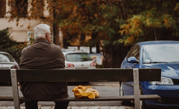 An old man suffering from Parkinson's sitting on a bench