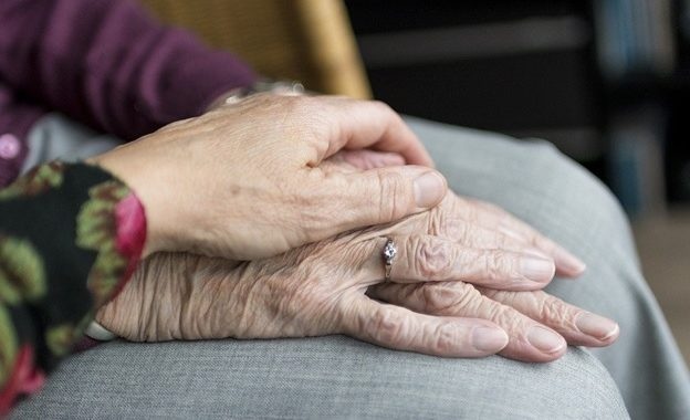 A woman holding the hand of an elderly lady