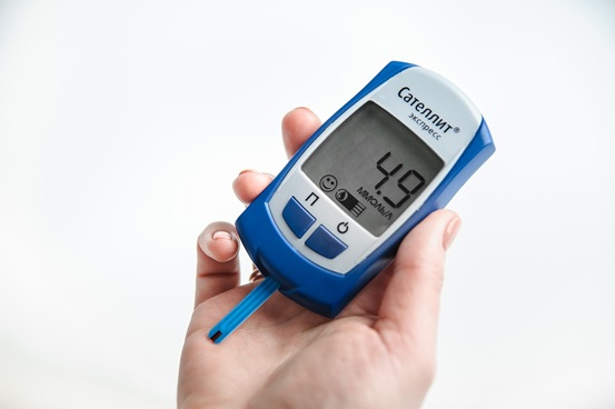 A person holding a Glucose meter