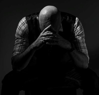A man feeling depressed and sitting with his head in his hands.
